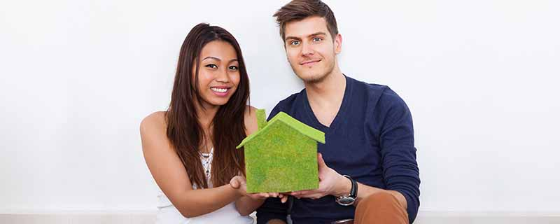 Portrait of young multiethnic couple holding green house model at new home